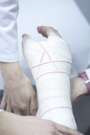 immobilize: Doctor applying a plaster cast and bandages to patient forearm and wrist to immobilize after fracture injury. Stock Photo