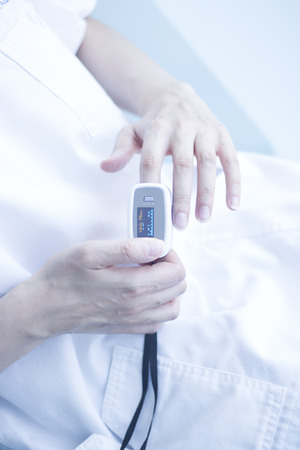 Blood pressure finger resting pulse monitor used to take heart rate and irregular beats with cardiogram.