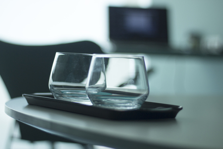Luxury five star hotel bedroom water or whisky drinking glasses on table on tray.