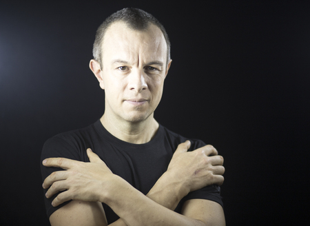 graying: Attractive  handsome slim healthy man aged in 40s in black t-shirt against plain black studio portrait background. Stock Photo