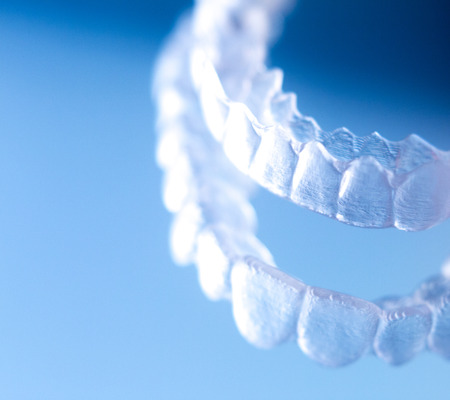 Invisible dental bracket aligners for modern orthodontic treatment to straighten teeth and improve dental hygiene. Stock Photo