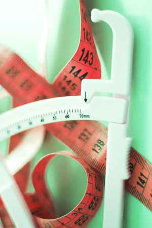 Fat caliper and measuring tape used to measure waistline, bodyfat levels for fitness and obesity checks.
