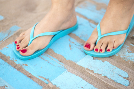 Ladys feet with red nail varnish in sandals on the sandy beach by the ocean in summer on wooden walkway. Reklamní fotografie