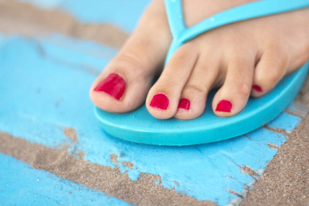 Ladys feet with red nail varnish in sandals on the sandy beach by the ocean in summer on wooden walkway. Stock Photo