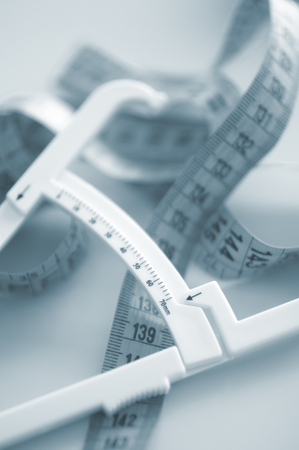centimetres: Fat caliper and measuring tape used to measure waistline, bodyfat levels for fitness and obesity checks.