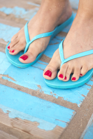 Lady's feet with red nail varnish in sandals on the sandy beach by the ocean in summer on wooden walkway.