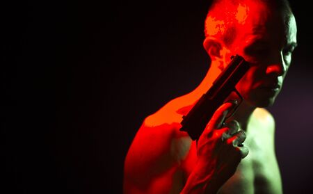 Man in dark with pistol gun nude looking menacing and scary like a killer or assassin