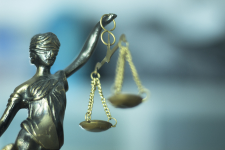 criminal: Legal law firm bronze statue of the goddess themis with scales of justice in attorneys office.