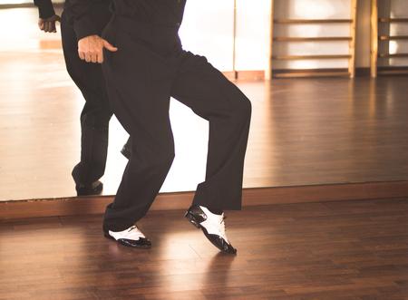 Ballroom dance male dancer and teacher in studio school dancing in rehearsal.