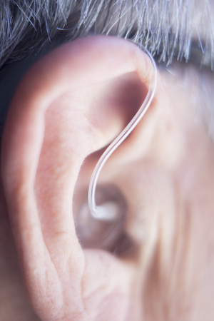 Modern digital in the ear hearing aid for deafness and the hard of hearing in aged man's ear. Foto de archivo