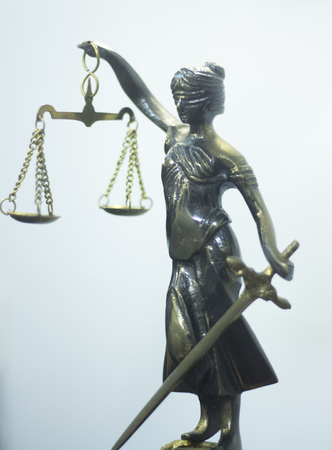 Legal law firm bronze statue of the goddess themis with scales of justice in attorneys office.