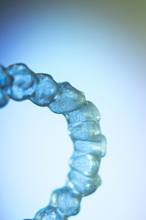 Invisible teeth retainers orthodontic brackets. Plastic modern straighterners to correct tooth alignment.