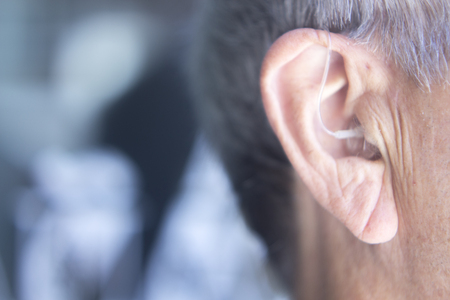 Modern digital in the ear hearing aid for deafness and the hard of hearing in aged man's ear. Archivio Fotografico
