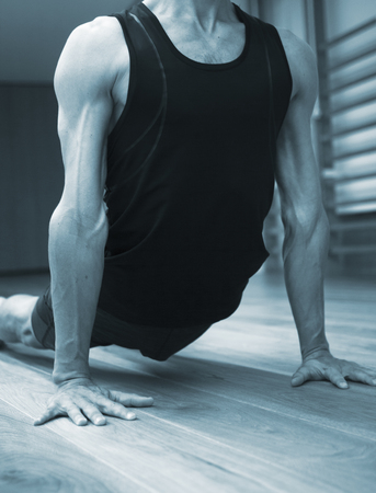 Man yoga teacher practising in gym fitness studio doing advanced asana posture.