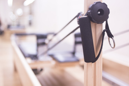 Reformer pilates studio machine for fitness workouts in gym. Stock Photo
