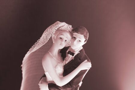 Bride and bridegroom wedding cake topper plastic statues holding after marriage ceremony.
