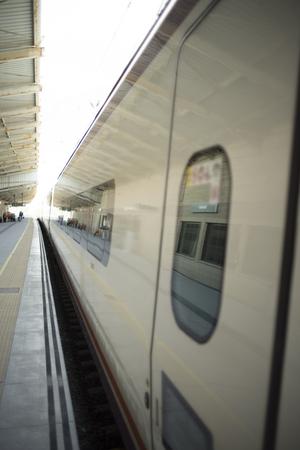 High speed modern bullet passenger train in station by platform in Spain. Stock Photo