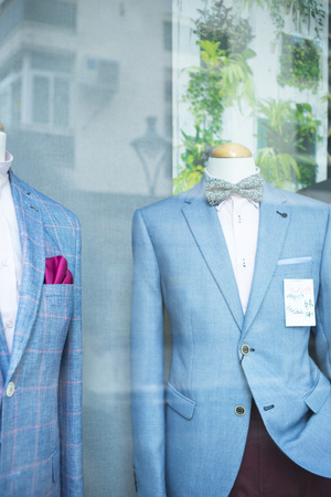 Tailors shop window made to measure suit store dummy mannequin with formal attire shirt on sale.