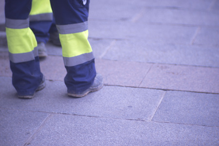 Municipal workers on sidewalk pavement standing in work uniform with hard toe boots and reflective strips..