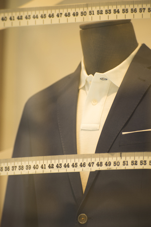 Tailor's shop window made to measure tailored suit store mannequin with formal shirt and tie with measuring tape.