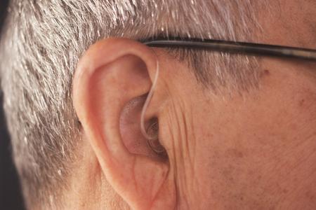 Deaf senior citizen man wearing modern digital high technology hearing aid in ear. Stock Photo