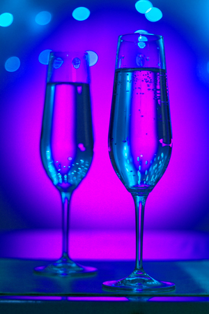 Champagne sparkling wine glasses of prosecco cava in nightclub party bar during wedding in Ibiza Spain with lights behind. Stock Photo