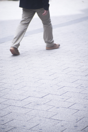 A man walking in busy urban city shopping street sidewalk pavement shoes feet and legs.