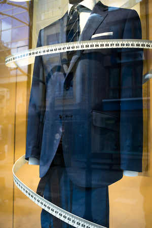 Tailors shop window made to measure tailored suit store mannequin with formal shirt and tie with measuring tape.