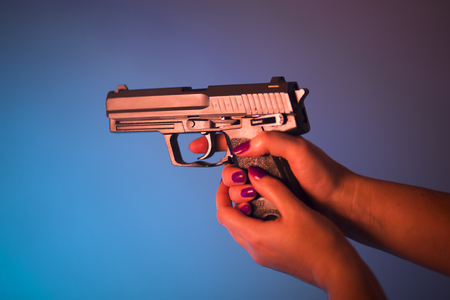 Womans hand holding automatic pistol gun. Stock Photo