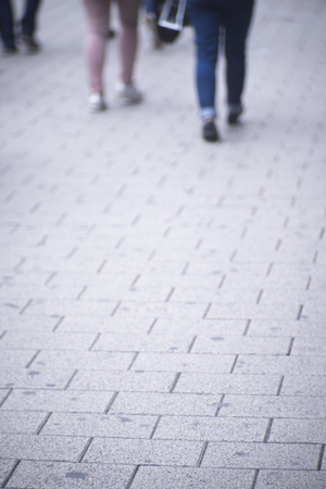 People walking in busy urban city shopping street sidewalk pavement shoes feet and legs. Stock Photo