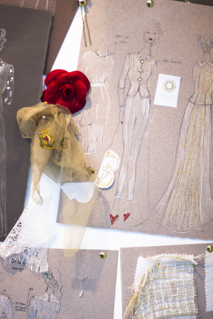Bridal store hand made dress shop window with drawings, thread and material for sewing.