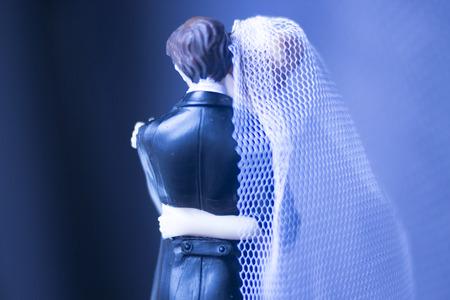 Wedding couple marriage cake topper plastic figures with tuxedo evening suit, white weddding dress veil. Stock Photo