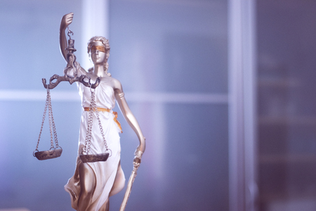 Law office legal justice statue of blind goddess Themis with scales in lawyers office.