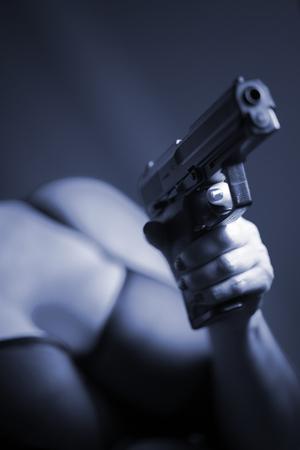 Sexy busty lady killer in lingerie underwear bra with handgun automatic pistol. Stock Photo