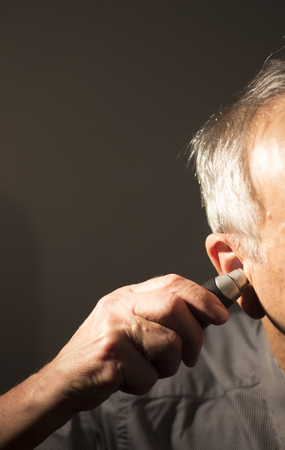 Senior citizen man cutting inner ear hair with electric cutter.