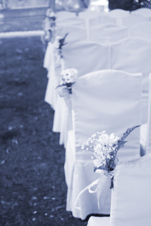 Outdoor summer garden civil wedding seating with flower bouquets decorated for marriage service.