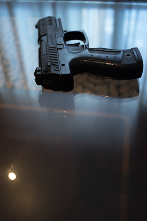 Automatic pistol gun on glass table in bedroom in luxury hotel in silhouette with reflection of window light.