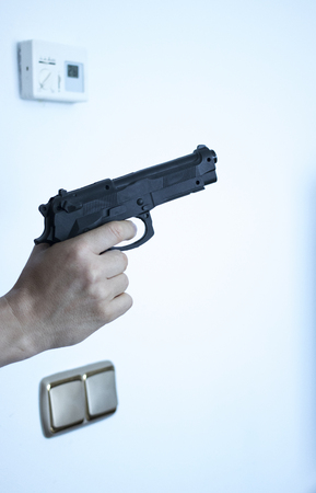 Hand holding automatic pistol gun in bedroom in luxury hotel in silhouette with window light. Stock Photo