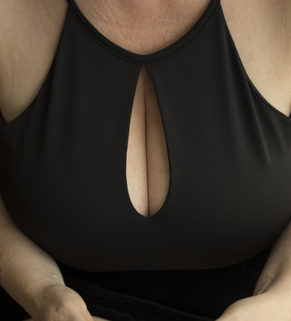Sexy and sensual big bust curvy breasts woman in little black dress with low cut top showing boobs cleavage.