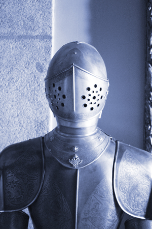 Medieval metal suit of armour and helmet worn by knight in middle ages castle. Stockfoto