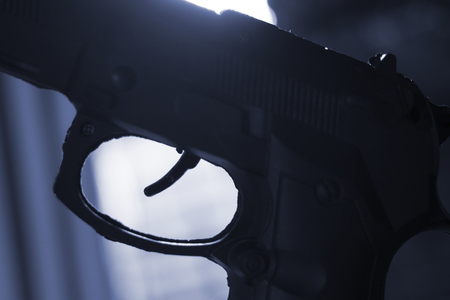 Pistol automatic handgun weapon in silhouette in atmospheric dark dramatic photo.