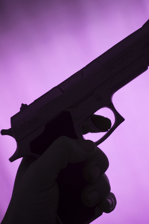 Pistol automatic handgun weapon in silhouette in hand of killer atmospheric dark dramatic photo. 免版税图像