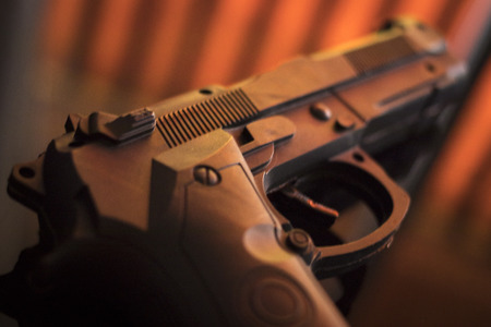 Pistol automatic handgun weapon on table in hotel bedroom in atmospheric dark dramatic photo. Stock fotó