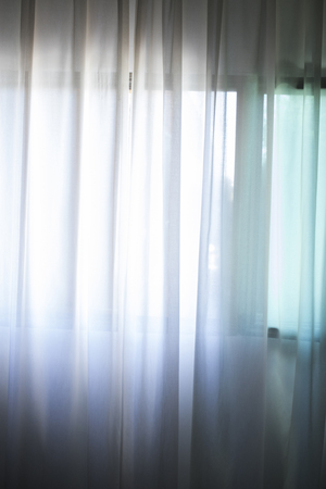 Hotel bedroom net curtains window with soft dalylight light.