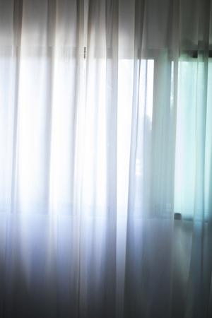 Hotel slaapkamer vitrages venster met zacht dalraam licht. Stockfoto