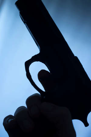 Pistol automatic handgun weapon in silhouette in hand of killer atmospheric dark dramatic photo. Archivio Fotografico