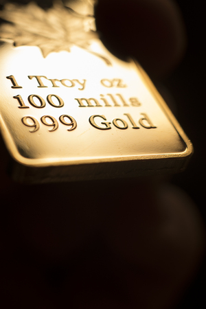 Fine solid gold 999.9 one ounce bullion ingot precious metals bar closeup isolated photo.