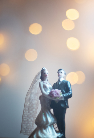 Wedding ceremony marriage bride groom cake topper figures with lights isolated.