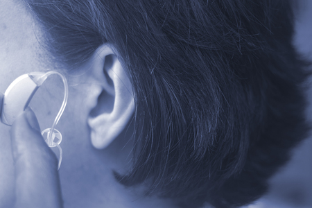 Deaf middle aged lady wearing modern digital high technology hearing aid in ear.