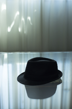 Typical retro style spy detective novel scene of  trilby hat on glass coffee table